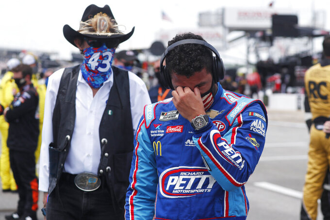 Driver Bubba Wallace, right, is overcome with emotion as he and team owner Richard Petty walk to his car in the pits of the Talladega Superspeedway prior to the start of the NASCAR Cup Series auto race at the Talladega Superspeedway in Talladega Ala., Monday June 22, 2020. In an extraordinary act of solidarity with NASCAR's only Black driver, dozens of drivers pushed the car belonging to Bubba Wallace to the front of the field before Monday's race as FBI agents nearby tried to find out who left a noose in his garage stall over the weekend. (AP Photo/John Bazemore)