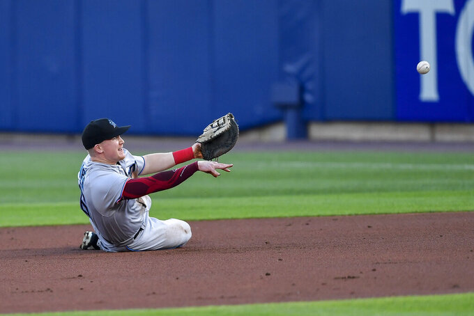 Miami Marlins first baseman Garrett Cooper (26) throws from the ground after fielding a grounder hit by Toronto Blue Jays' Joe Panik, who was out at first during the second inning of a baseball game in Buffalo, N.Y., Tuesday, June 1, 2021. (AP Photo/Adrian Kraus)