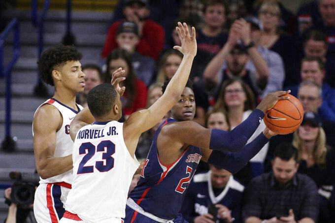 Saint Mary's forward Malik Fitts, right, looks to pass while defended by Gonzaga guard Zach Norvell Jr. (23) and forward Jeremy Jones during the second half of an NCAA college basketball game in Spokane, Wash., Saturday, Feb. 9, 2019. Gonzaga won 94-46. (AP Photo/Young Kwak)