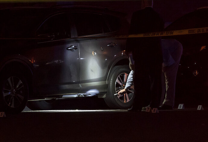 In this Wednesday, Sept. 18, 2019 photo, investigators looked at what appears to be bullet holes in a car door at the scene of a homicide in St. Paul, Minn. (Renee Jones Schneider/Star Tribune via AP)