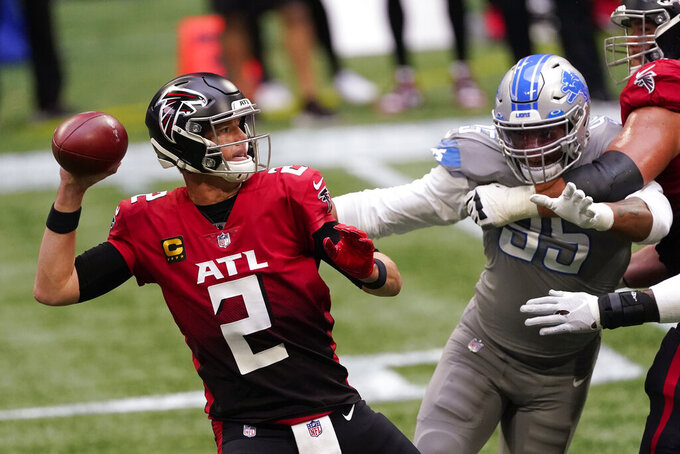 Atlanta Falcons quarterback Matt Ryan (2) works as Detroit Lions defensive end Romeo Okwara (95) pressures during the first half of an NFL football game, Sunday, Oct. 25, 2020, in Atlanta. (AP Photo/John Bazemore)