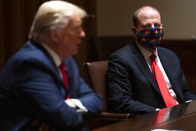 Colorado Gov. Jared Polis listens as President Donald Trump speaks during a meeting on the coronavirus response, in the Cabinet Room of the White House, Wednesday, May 13, 2020, in Washington. (AP Photo/Evan Vucci)