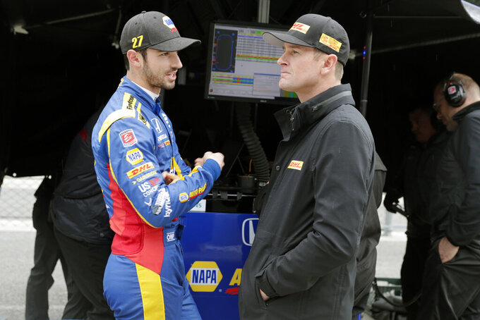IndyCar drivers Alexander Rossi, left, and Ryan Hunter-Reay talks during a rain delay during auto racing testing at the Indianapolis Motor Speedway in Indianapolis, Wednesday, April 24, 2019. (AP Photo/Michael Conroy)
