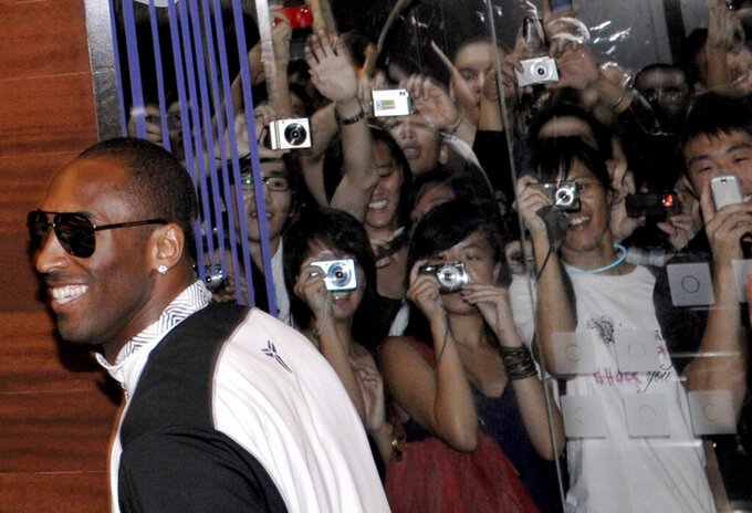 FILE - In this July 22, 2009, file photo, NBA star Kobe Bryant walks past fans as he enters a Nike store in Singapore. (AP Photo/Joseph Nair, File)