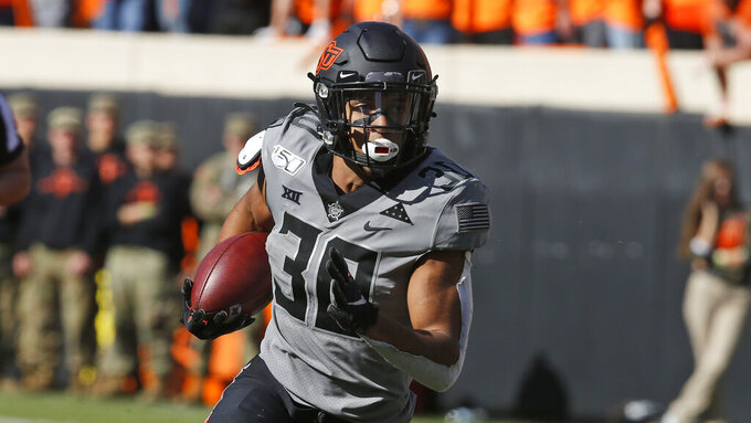 FILE - In this Saturday, Nov. 16, 2019, file photo, Oklahoma State running back Chuba Hubbard (30) carries against Kansas during an NCAA college football game in Stillwater, Okla., Saturday, Nov. 16, 2019. Oklahoma State has high hopes with Heisman contender Chuba Hubbard and star receiver Tylan Wallace. (AP Photo/Sue Ogrocki)