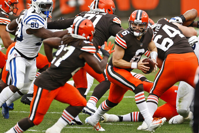 Cleveland Browns quarterback Baker Mayfield looks to hand off during the first half of an NFL football game against the Indianapolis Colts, Sunday, Oct. 11, 2020, in Cleveland. (AP Photo/Ron Schwane)