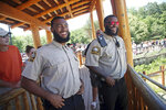In this July 6, 2018, photo, University of Minnesota football players Jerry Gibson, right, and Winston DeLattiboudere are shown working as security guards this summer at the Como Park Zoo and Conservatory for the city of St. Paul, Minn., a few miles from the university campus. One of the Gophers coaches connected them to the opportunity. (AP Photo/Jim Mone)