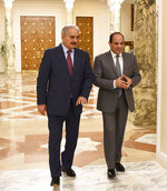 FILE - In this May 9, 2019 file photo, provided by Egypt's presidency media office, Egyptian President Abdel-Fattah el-Sissi, right, walks with Field Marshal Khalifa Hifter, the head of the self-styled Libyan National Army, in Cairo, Egypt. Libya's eastern city of Benghazi finally feels safe again, but the city center lies in ruins, thousands of people remain displaced, and forces loyal to  Hifter, who now controls eastern Libya, have cracked down on dissent. Hifter has modeled his rule on that of el-Sissi, his close ally in neighboring Egypt. Both have declared war on terrorism -- applying the term not only to extremist groups but more moderate Islamists. (Egyptian Presidency Media office via AP, File)