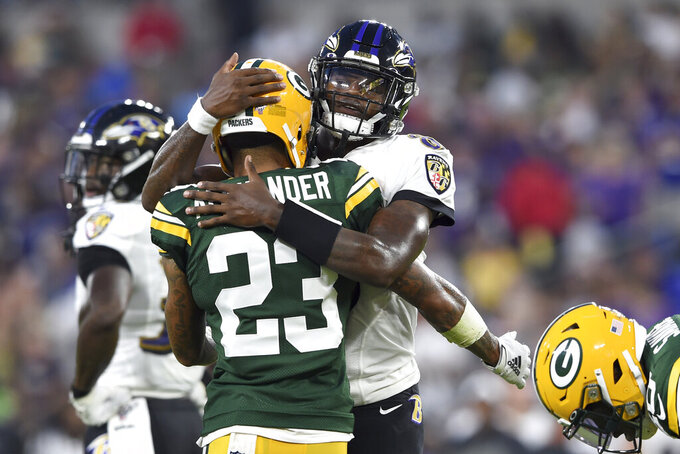 Baltimore Ravens quarterback Lamar Jackson, right, hugs Green Bay Packers cornerback Jaire Alexander (23) after a play during the first half of a NFL football preseason game, Thursday, Aug. 15, 2019, in Baltimore. (AP Photo/Gail Burton)
