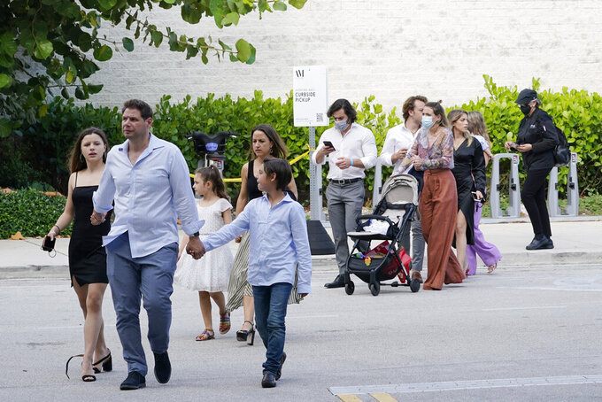 Shoppers who were hiding in stores exit the Aventura Mall after a shooting left three people injured and several suspects in custody, Saturday, May 8, 2021, in Aventura, Fla. Aventura Police said two groups of people had begun fighting in the mall when shots rang out. (AP Photo/Marta Lavandier)