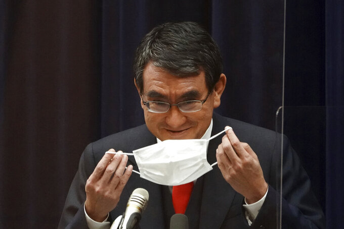"""Japan's Administrative Reform Minister Taro Kono, who is also in charge of COVID-19 vaccines, puts his mask back on after a news conference in Tokyo on Tuesday, Feb. 16, 2021, on  inoculations. Japan rolls out its vaccination campaign Wednesday, Feb. 17, after the government gave belated first approval to a shot co-developed by Pfizer Inc. that the U.S. and many other countries started using two months ago. Kono defended the delay. """"It was more important for the government to show the Japanese people that everything was done"""" to encourage taking the vaccines, he said. (AP Photo/Eugene Hoshiko)"""