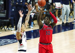 St. John's forward Marcellus Earlington (10) scores against Connecticut guard Tyrese Martin (4) in the second half of an NCAA college basketball game in Storrs, Conn., Monday, Jan. 18, 2021.  (David Butler II/Pool Photo via AP)