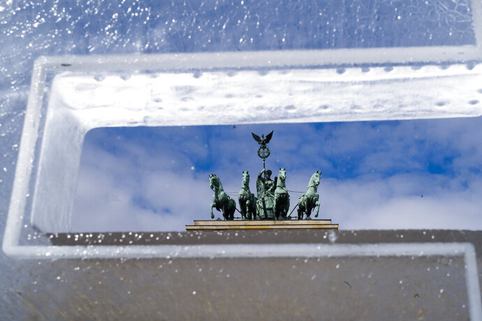 The Brandenburg Gate stands behind an ice block set up by Climate activists in Berlin, Germany, Tuesday, May 14, 2019. The ice block is part of a slogan reading 'Last Exit' set up by Greenpeace in front of the Brandenburg Gate as a protest in reference to the 'Petersberg climate talks'. (AP Photo/Markus Schreiber)