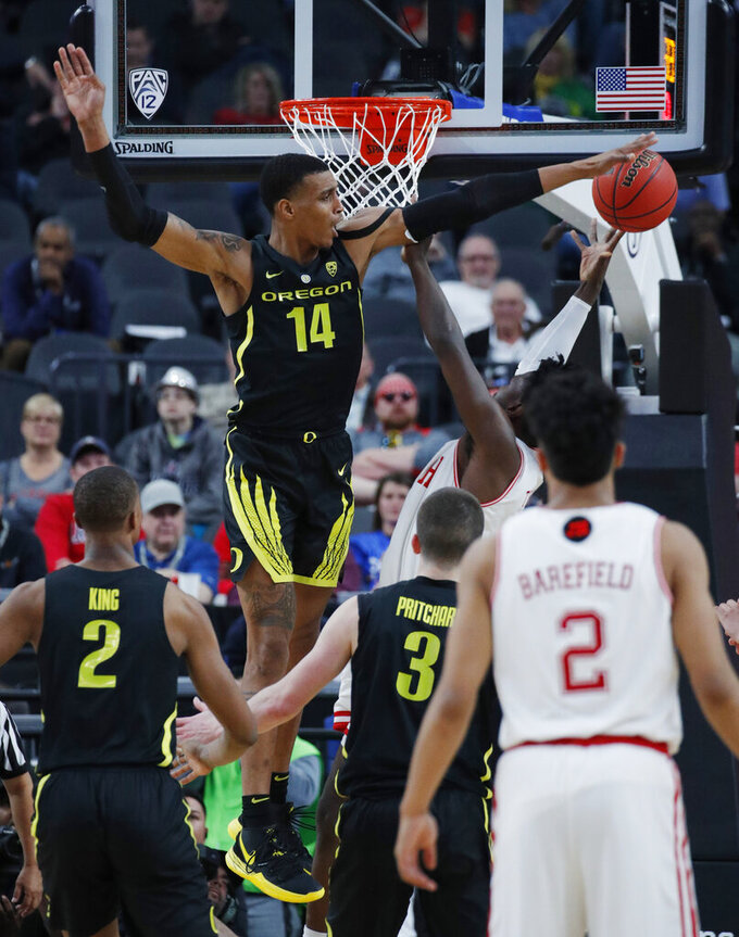 Oregon's Kenny Wooten (14) tries to block a shot by Utah during the second half of an NCAA college basketball game in the quarterfinals of the Pac-12 men's tournament Thursday, March 14, 2019, in Las Vegas. (AP Photo/John Locher)