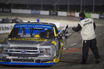 A race official hands Grant Enfinger the checkered flag after Enfinger won the NASCAR Truck Series auto race at Martinsville Speedway in Martinsville, Va., Friday, Oct. 30, 2020. (AP Photo/Lee Luther Jr.)