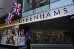 A woman walks past the Debenhams flagship department store on Oxford Street, during England's second coronavirus lockdown in London, Tuesday, Dec. 1, 2020. In another dark day for the British retailing industry, Debenhams said Tuesday it will start liquidating its business after a potential buyer of the company pulled out, a move that looks like it will cost 12,000 workers their jobs. (AP Photo/Matt Dunham)