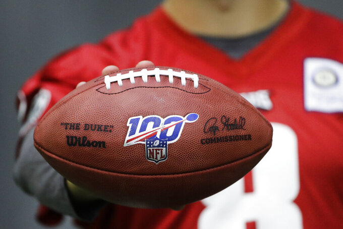 "In this Oct. 17, 2019, photo, Philadelphia Eagles practice squad quarterback Kyle Lauletta displays a football during an interview with The Associated Press at the NFL football team's training facility in Philadelphia. Those shiny ""NFL 100"" logos on all the footballs being used to commemorate the league's centennial season are part of a lengthy process that goes into making each handcrafted leather game ball. Wilson has been the official game ball of the NFL since 1941. The size, shape and feel of the football have evolved over the years, but the personal touch remains the same.(AP Photo/Matt Rourke)"