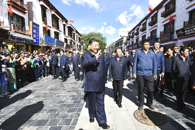 In this July 22, 2021 photo released by China's Xinhua News Agency, Chinese President Xi Jinping, center, visits Barkhor Street near the Jokhang Temple in Lhasa in western China's Tibet Autonomous Region. Chinese leader Xi Jinping has made a rare visit to Tibet as authorities tighten controls over the Himalayan region's traditional Buddhist culture, accompanied by an accelerated drive for economic development. (Xie Huanchi/Xinhua via AP)