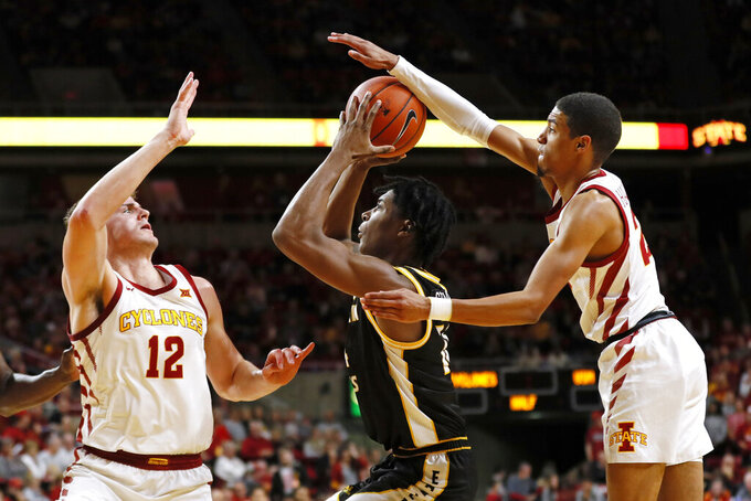 Southern Mississippi forward Tyler Stevenson, center, shoots between Iowa State's Michael Jacobson, left, and Tyrese Haliburton, right, during the second half of an NCAA college basketball game, Tuesday, Nov. 19, 2019, in Ames, Iowa. (AP Photo/Charlie Neibergall)