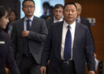 Song Liuping, right, chief legal officer of Huawei, arrives for a press conference at Huawei's campus in Shenzhen in southern China's Guandong Province, Thursday, Dec. 5, 2019. Chinese tech giant Huawei is asking a U.S. federal court to throw out a rule that bars rural phone carriers from using government money to purchase its equipment on security grounds. (AP Photo/Mark Schiefelbein)