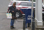 A woman drops off a letter in a mailbox in front of the post office as a storm packing high winds and snow sweeps through the intermountain West Tuesday, Sept. 8, 2020, in Georgetown, Colo. Forecasters predict that the storm will continue through Wednesday before moving out on to the plains. (AP Photo/David Zalubowski)
