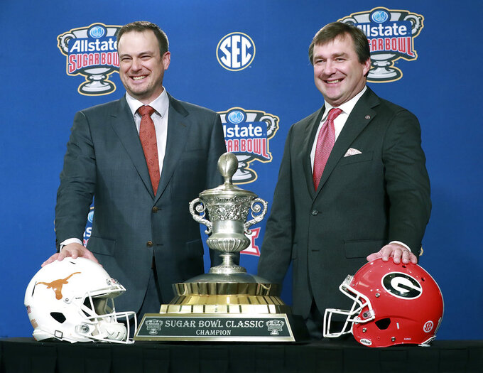 Georgia head coach Kirby Smart, right, and Texas head coach Tom Herman laugh during their photo opportunity with the Sugar Bowl trophy at a press conference on Monday, Dec 31, 2018, in New Orleans. (Curtis Compton/Atlanta Journal-Constitution via AP)