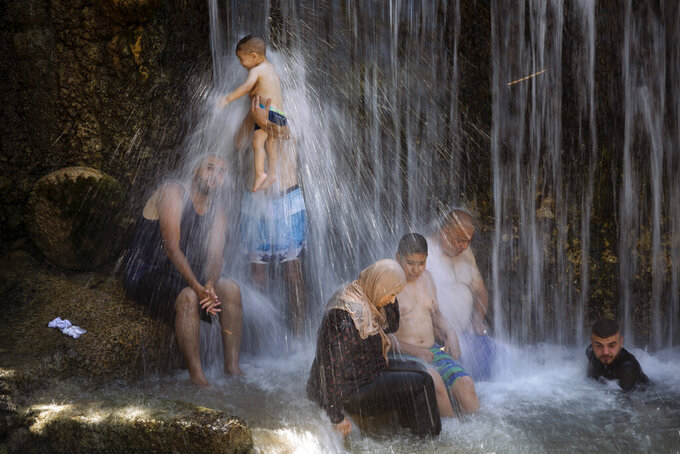 """Israeli Arabs stand under a waterfall during the Muslim Eid al-Adha holiday at the Gan HaShlosha national park near the northern Israeli town of Beit Shean, Wednesday, July 21, 2021. Eid al-Adha meaning """"Feast of Sacrifice,"""" this most important Islamic holiday marks the willingness of the Prophet Ibrahim (Abraham to Christians and Jews) to sacrifice his son.  (AP Photo/Oded Balilty)"""