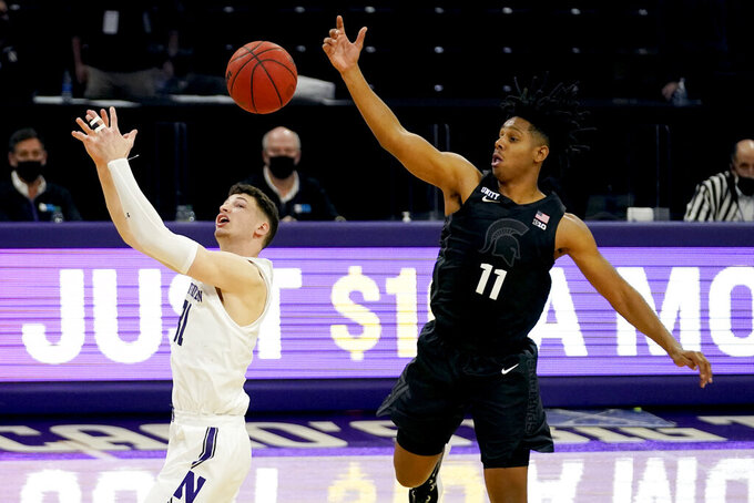 Northwestern forward Robbie Beran, left, and Michigan State guard A.J. Hoggard battle for a loose ball during the second half of an NCAA college basketball game in Evanston, Ill., Sunday, Dec. 20, 2020. Northwestern won 79-65. (AP Photo/Nam Y. Huh)