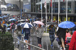 Spectators walk in the rain as play is stopped don the outside courts during their first round singles matches at the Australian Open tennis championship in Melbourne, Australia, Monday, Jan. 20, 2020. (AP Photo/Andy Brownbill)