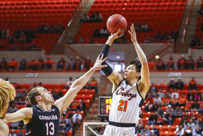 Oklahoma State's Lindy Waters shoots a 3-point shot over South Carolina's Felipe Haase during an NCAA college basketball game, Saturday, Jan. 26, 2019, in Stillwater, Okla. (Devin Lawrence Wilber/Tulsa World via AP)