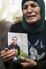 Rana, mother of Iyad Halak, 32, holds his photo at their home in East Jerusalem's Wadi Joz, Saturday, May 30, 2020. Israeli police shot dead a Palestinian near Jerusalem's Old City who they had suspected was carrying a weapon but turned out to be unarmed. A relative said Halak was mentally disabled and was heading to a nearby school for people with special needs. (AP Photo/Mahmoud Illean)