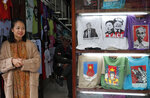 In this Feb. 24, 2019, photo, a woman stand next to t-shirts featuring U.S. President Donald Trump and North Korean leader Kim Jong Un ahead of the North Korea-U.S. summit in Hanoi, Vietnam. The summit this week between Kim Jong Un and Donald Trump may be a chance to advance the cause of world peace. For canny entrepreneurs, though, it's an opportunity to make a buck - or a dong, in Vietnamese currency. A U.S presidential visit is a big deal anywhere, and enterprising folks take note. Drinks will be poured, burgers will be broiled and T-shirts will be silkscreened.(AP Photo/Vincent Yu)