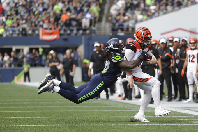 Seattle Seahawks defensive end Jadeveon Clowney, left, tackles Cincinnati Bengals quarterback Andy Dalton, right, during the second half of an NFL football game, Sunday, Sept. 8, 2019, in Seattle. (AP Photo/Stephen Brashear)