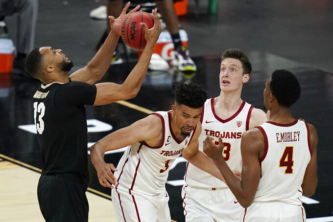 Colorado's Dallas Walton, left, grabs a rebound over Southern California's Isaiah Mobley (3), Drew Peterson (13) and Evan Mobley (4) during the second half of an NCAA college basketball game in the semifinal round of the Pac-12 men's tournament Friday, March 12, 2021, in Las Vegas. (AP Photo/John Locher)
