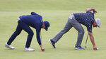 United States' Jordan Spieth, left and United States' Bryson DeChambeau right repair pitch marks on the 18th green during the first round British Open Golf Championship at Royal St George's golf course Sandwich, England, Thursday, July 15, 2021. (AP Photo/Ian Walton)