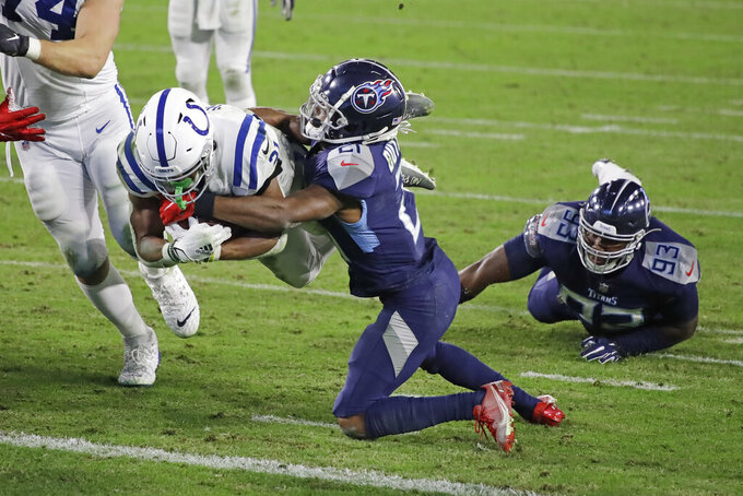 Indianapolis Colts running back Nyheim Hines, left, dives past Tennessee Titans cornerback Malcolm Butler, center, for a touchdown in the second half of an NFL football game Thursday, Nov. 12, 2020, in Nashville, Tenn. (AP Photo/Ben Margot)