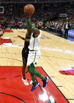 Boston Celtics guard Kyrie Irving (11) goes to the basket as Chicago Bulls guard Kris Dunn (32) defends him during the first half of an NBA basketball game Saturday, Feb. 23, 2019, in Chicago. (AP Photo/David Banks)