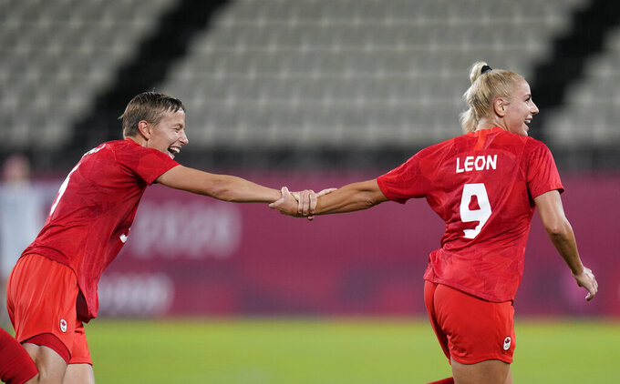 Canada's Adriana Leon, right, celebrates with teammate Quinn after scoring her side's opening goal against Great Britain during a women's soccer match at the 2020 Summer Olympics, Tuesday, July 27, 2021, in Kashima, Japan. (AP Photo/Fernando Vergara)