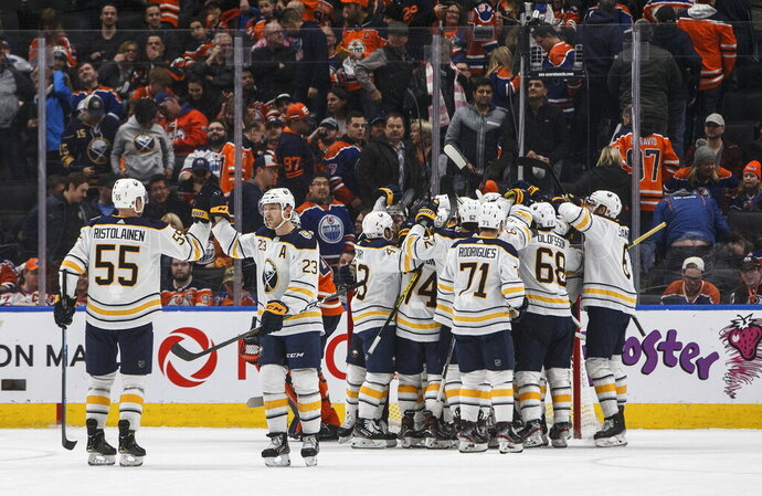 Buffalo Sabres players celebrate the overtime goal against the Edmonton Oilers after an NHL hockey game, Sunday, Dec. 8, 2019 in Edmonton, Alberta. (Jason Franson/The Canadian Press via AP)