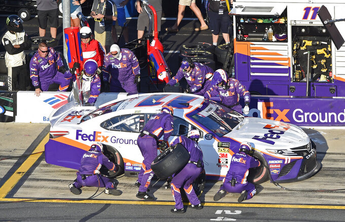 Crew members perform a pit stop on Denny Hamlin's car during a NASCAR Cup Series auto race at Charlotte Motor Speedway in Concord, N.C., Sunday, May 26, 2019. (AP Photo/Mike McCarn)