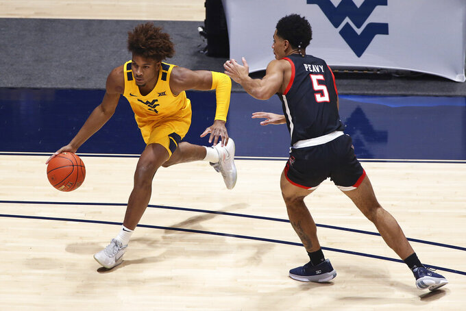 West Virginia guard Miles McBride (4) is defend by Texas Tech guard Micah Peavy (5) during the first half of an NCAA college basketball game Monday, Jan. 25, 2021, in Morgantown, W.Va. (AP Photo/Kathleen Batten)