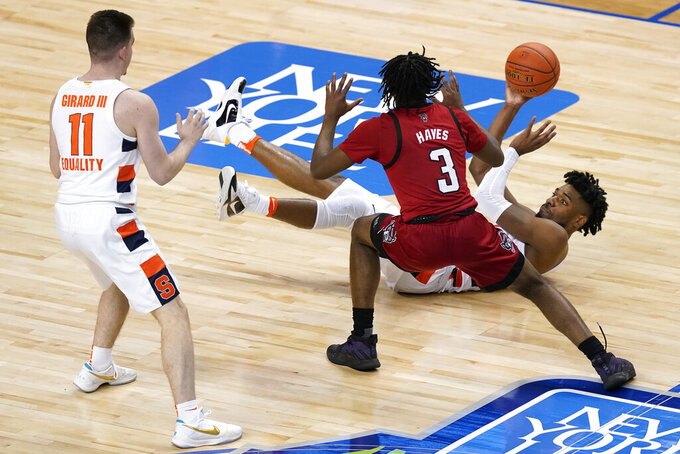 Syracuse forward Quincy Guerrier, right, looks to pass the ball to teammate guard Joseph Girard III (11) as North Carolina State guard Cam Hayes (3) defends during the second half of an NCAA college basketball game in the second round of the Atlantic Coast Conference tournament in Greensboro, N.C., Wednesday, March 10, 2021. (AP Photo/Gerry Broome)
