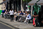 People sit at outdoor tables at a restaurant in Soho, in London, Monday, June 14, 2021. British Prime Minister Boris Johnson is expected to confirm Monday that the next planned relaxation of coronavirus restrictions in England will be delayed as a result of the spread of the delta variant first identified in India. (AP Photo/Alberto Pezzali)