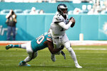 Miami Dolphins linebacker Charles Harris (90) attempts to tackle Philadelphia Eagles quarterback Carson Wentz (11), during the first half at an NFL football game, Sunday, Dec. 1, 2019, in Miami Gardens, Fla. (AP Photo/Brynn Anderson)