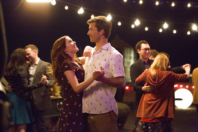 This image released by Netflix shows Zoey Deutch, left, and Glen Powell in a scene from