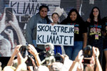 Climate activist Greta Thunberg, second from left, holding a sign, poses photos with other activists during a student-led climate change march in Los Angeles on Friday, Nov. 1, 2019. (AP Photo/Ringo H.W. Chiu)