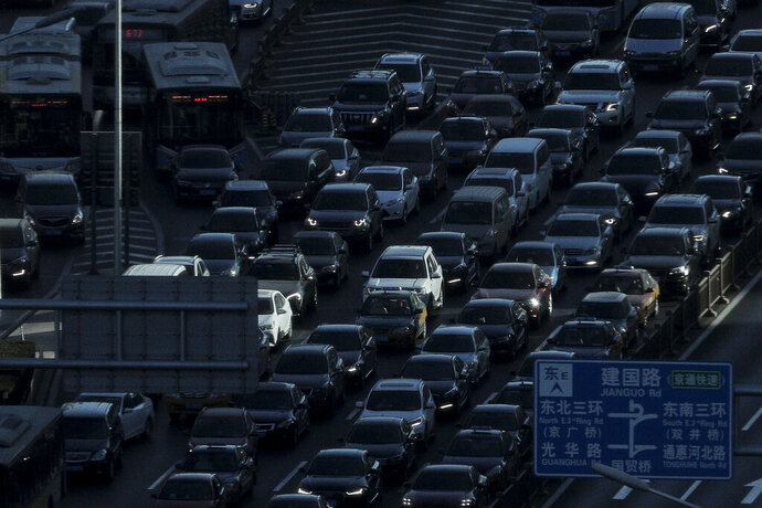 FILE - In this Dec. 11, 2018, file photo, a beam of sunlight is cast on vehicles on a city ring-road clogged with heavy traffic during the morning rush hour in Beijing. China's auto sales fell for an eighth month in January, 2019, extending a painful decline for the biggest global market. (AP Photo/Andy Wong, File)