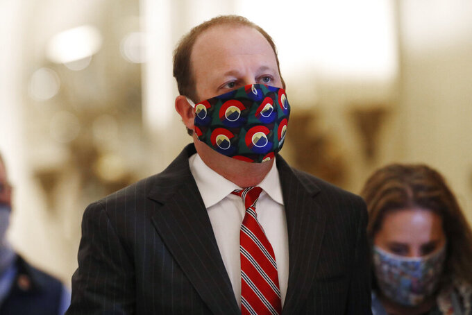 Colorado Governor Jared Polis wears a face mask as he heads into a news conference to update reporters on the state's efforts to stem the rise of the new coronavirus Wednesday, May 6, 2020, in Denver. (AP Photo/David Zalubowski)