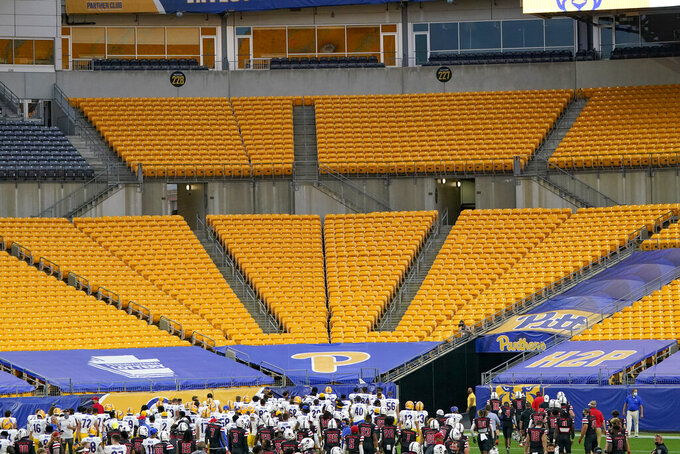 The Pittsburgh football team looks toward the empty bleachers after defeating Austin Peay in an NCAA college football game, Saturday, Sept. 12, 2020, in Pittsburgh. In a quirk this season, No. 5 Notre Dame enjoys a greater home-field advantage than most of its opponents: As of now, the Fighting Irish are slated to play in front of only one crowd bigger than their own, which is limited to about 10,000 people because of the pandemic. Pitt, Boston College, North Carolina and Wake Forest have not allowed any spectators to attend so far.  (AP Photo/Keith Srakocic)