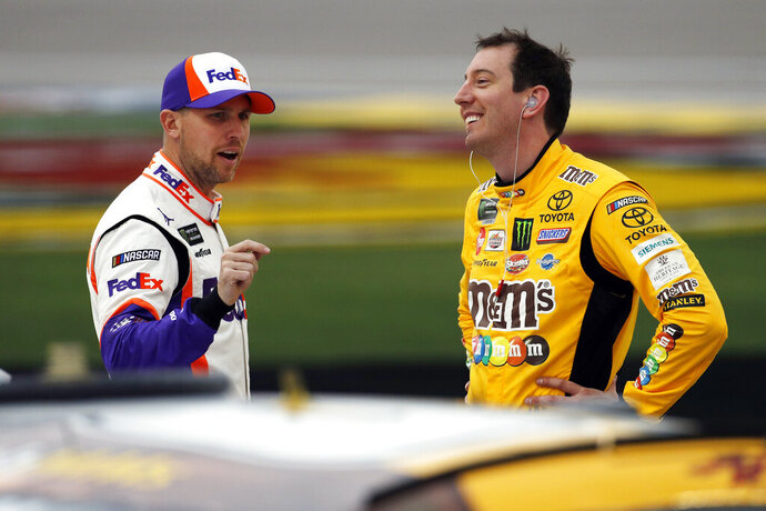 FILE - In this March 1, 2019, file photo, drivers Denny Hamlin, left, and Kyle Busch talk in pit lane before qualifying for the NASCAR Cup Series auto race at Las Vegas Motor Speedway in Las Vegas. Hamlin has all the momentum headed into the third round of NASCAR's playoffs, which start Sunday at Martinsville Speedway. But hot on his bumper are his Joe Gibbs Racing teammates, regular season champion Kyle Busch and Martin Truex Jr., who leads the series with six wins this season.(AP Photo/John Locher, File)